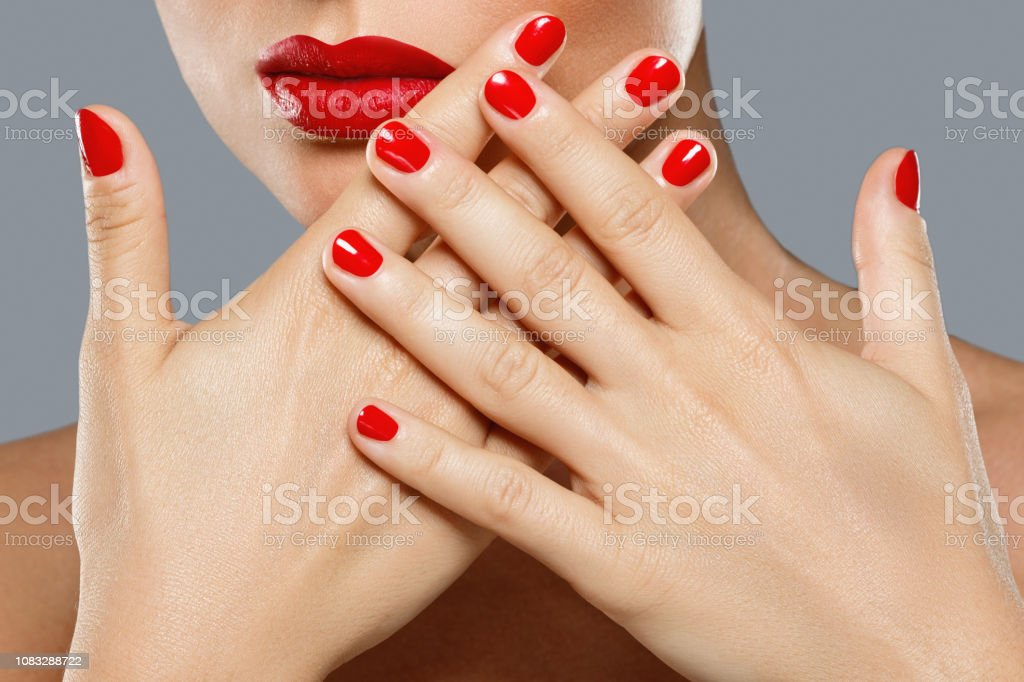 Beauty and cosmetics. Close-up of female mouth and nails with red...