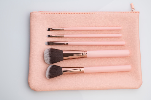 High resolution image of make up brushes and pink pouch on white background shot in studio