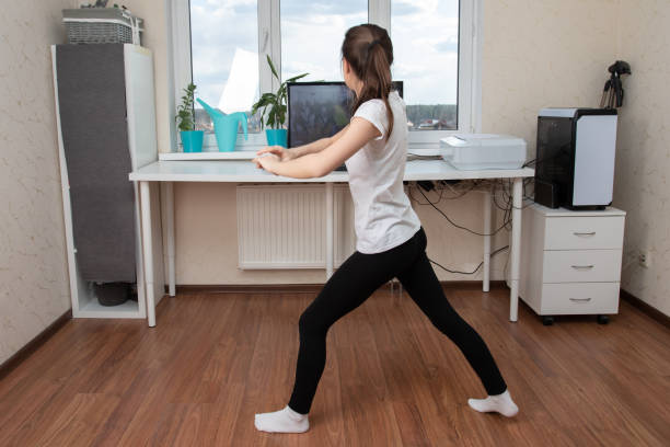 Beauty and health at home during a pandemic quarantine. Young woman dancing online on the internet stock photo