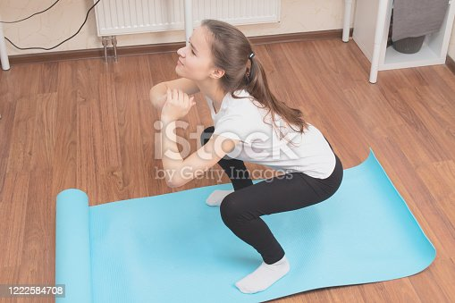 925799546 istock photo Beauty and health at home during a pandemic quarantine. Young woman doing exercises looking at the monitor 1222584708