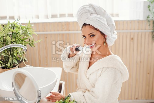 istock Beauty and health care concept. Attractive young smiling woman in bathrobe holds a toothbrush in the hand and looks at the camera. 1167975126