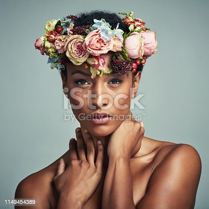 Studio portrait of a beautiful young woman wearing a floral head wreath against a grey background