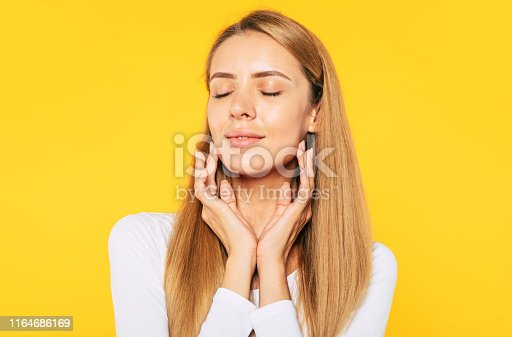 628536910 istock photo Beauty and tenderness. Close up portrait of gorgeous blonde woman with closed eyes while she is touching skin on her face. 1164686169