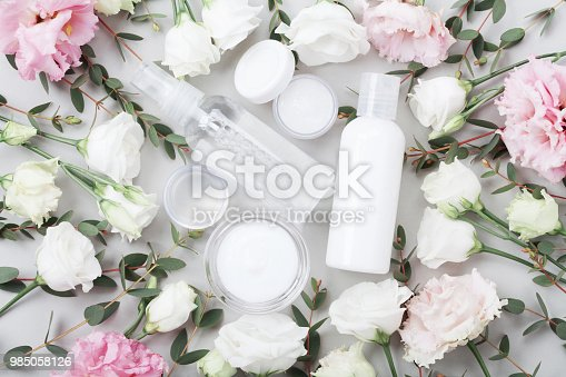 927626522 istock photo Beauty and wellness background from natural cosmetic decorated with flowers and eucalyptus leaves on table top view. 985058126