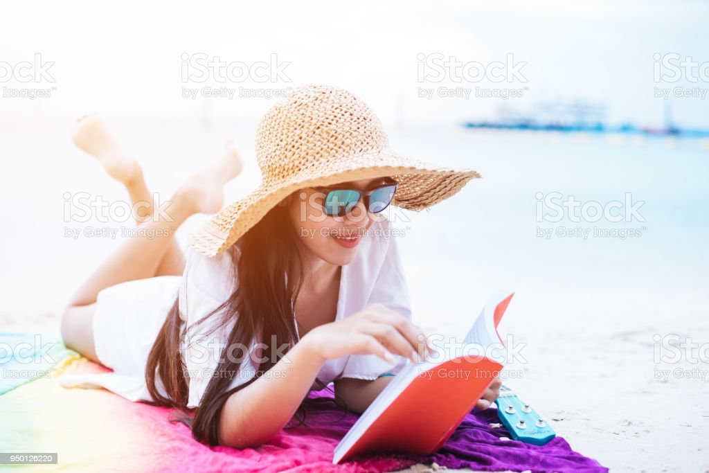 Beauty Asian woman have vacation on beach. Girl wearing wing hat and reading book on colorful mat near sea. Lifestyle and happy life concept. Travel and holiday theme. stock photo