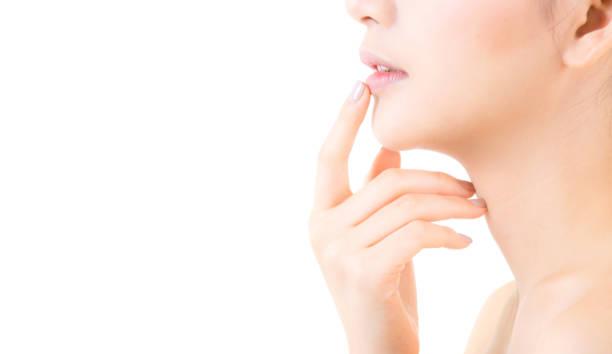 junge asiatin schönheit mit frische und saubere haut lippen berühren. kosmetik, beauty & spa-konzept. modell halten sie einen finger in den mund. - labello stock-fotos und bilder