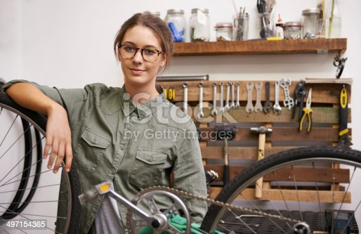Cropped shot of a young woman leaning on a bicycle at work