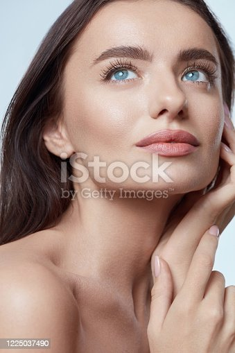 Beauty. Beautiful Woman Touching Face Close Up Portrait. Blue-Eyed Brunette Model With Perfect Skin And Natural Makeup Looking Away.