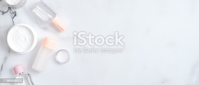 1128479585 istock photo Beauty blog banner with cosmetic cream and lotion bottles on marble background. Top view, flat lay, copy space. Hand skin care, spa cosmetic products concept 1199956502