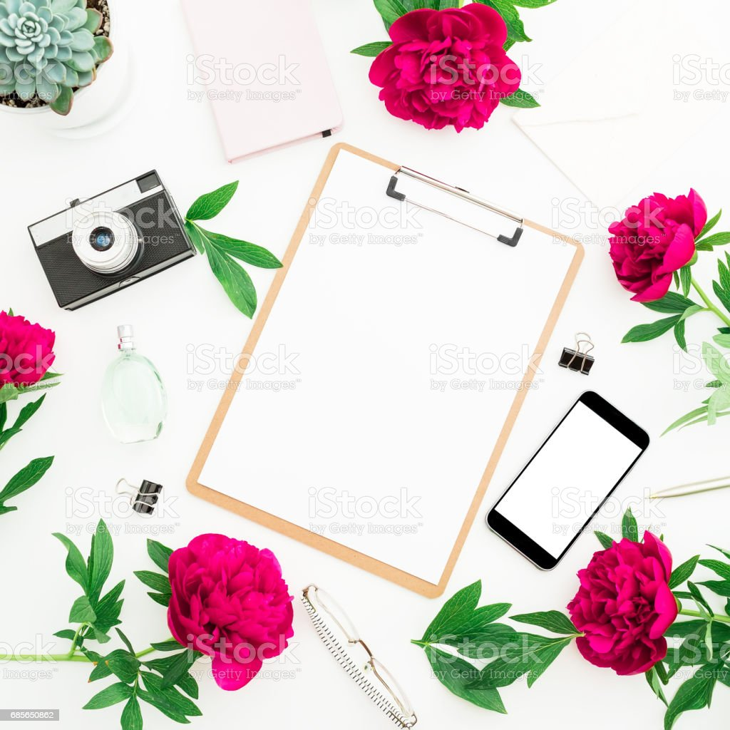 Beauty blog concept. Blogger or freelancer workspace with clipboard, notebook, retro camera, peonies and mobile phone on white background. Flat lay, top view. foto de stock royalty-free