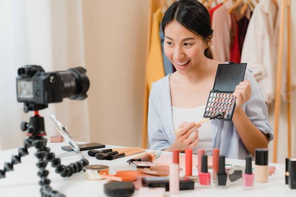 Beauty-Blogger präsentieren Beauty-Kosmetik sitzen in der Frontkamera für die Aufnahme von Video. Schöne asiatische Frau verwenden Kosmetik Bewertung Make-up Tutorial übertragen Live-Video in soziale Netzwerke durch das Internet. – Foto