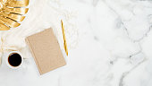 istock Beauty blogger workspace top view. Home office desk marble table with golden tropical monstera leaf, cup of coffee, gold paper notebook and pen. Flat lay, top view, copy space. 1192900021