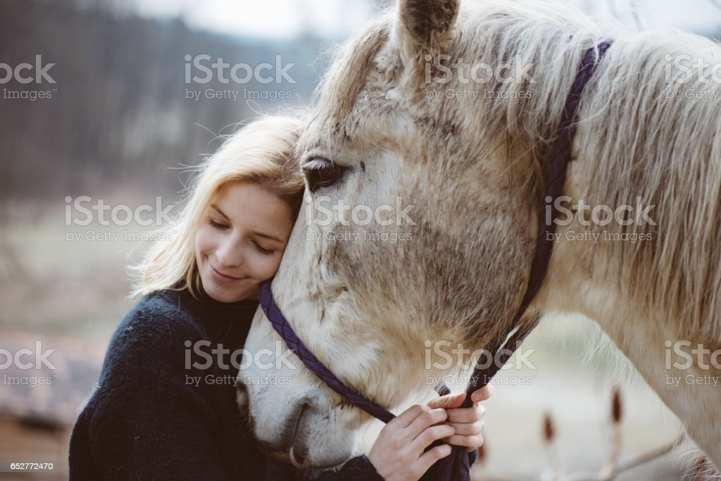 beauty blondie with horse. Young woman in love with her horse.