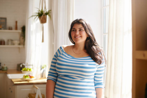 Beauty, bodypositivity, people and lifestyle concept. Indoor shot of gorgeous brunette Latin girl posing by window in kitchen dressed in xxl blue and white striped shirt, having joyful beaming smile Beauty, bodypositivity, people and lifestyle concept. Indoor shot of gorgeous brunette Latin girl posing by window in kitchen dressed in xxl blue and white striped shirt, having joyful beaming smile large stock pictures, royalty-free photos & images