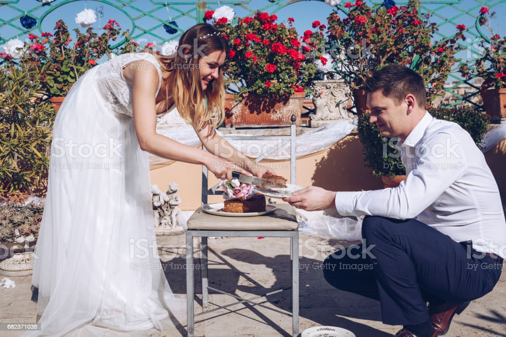 Schoonheid bruid en knappe bruidegom snijden een bruidstaart. Koppel op het terras met Rome stadsgezicht op de achtergrond. Mooi model meisje in witte jurk. Man in pak. royalty free stockfoto