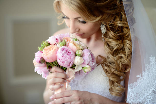 Beauty bride in bridal gown with bouquet and lace veil indoors stock photo