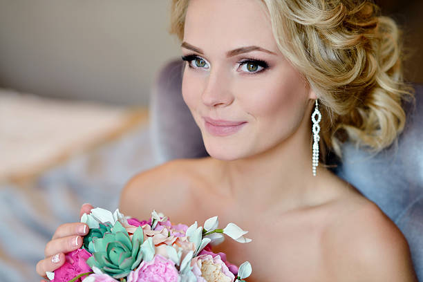 Beauty bride in bridal gown with bouquet and lace veil stock photo