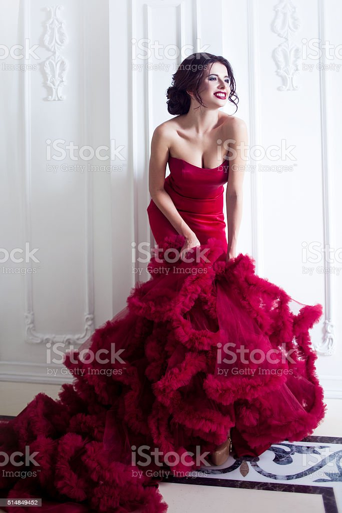 Beauty Brunette model woman in  evening red dress. Beautiful fashion stock photo