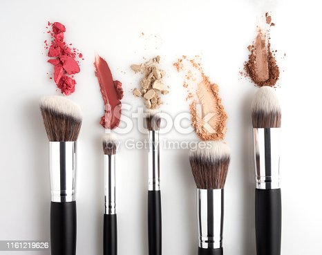 Creative concept beauty fashion photo of cosmetic product make up brushes kit with smashed lipstick eyeshadow on white background.