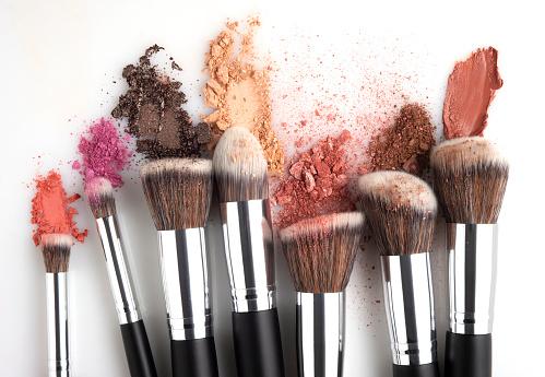 Creative concept beauty fashion photo of cosmetic product make up brushes kit with smashed lipstick eyeshadow on white background.