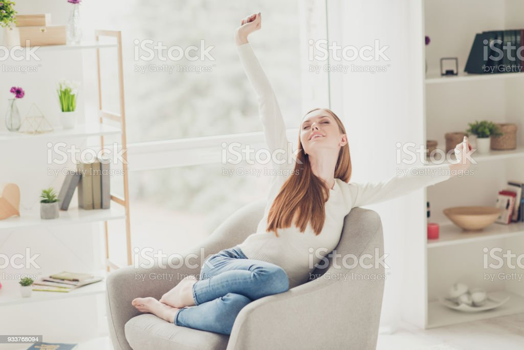 Beauty calm fashion lying denim happiness delight day-off sleep lounge chill concept. Cute sweet attractive gorgeous lovely woman wearing casual outfit stretching arms sitting on comfortable armchair stock photo