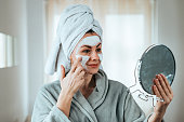 Beauty care concept. Beautiful woman applying face mask.