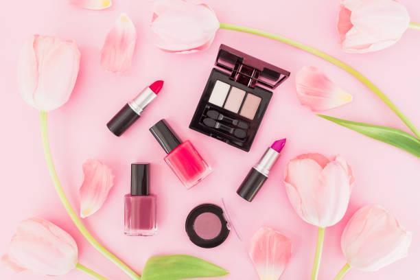 美麗的構圖與鬱金香花和化妝化妝品在粉紅色的背景。頂部視圖。平躺。 - 美容品 個照片及圖片檔