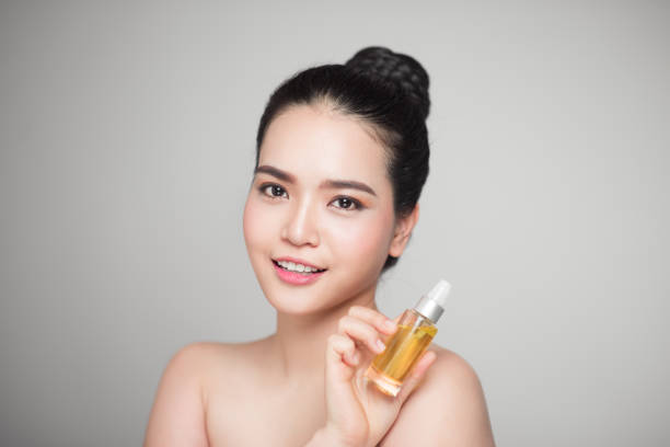beauty concept. asian pretty woman with perfect skin holding oil bottle - serum stock photos and pictures