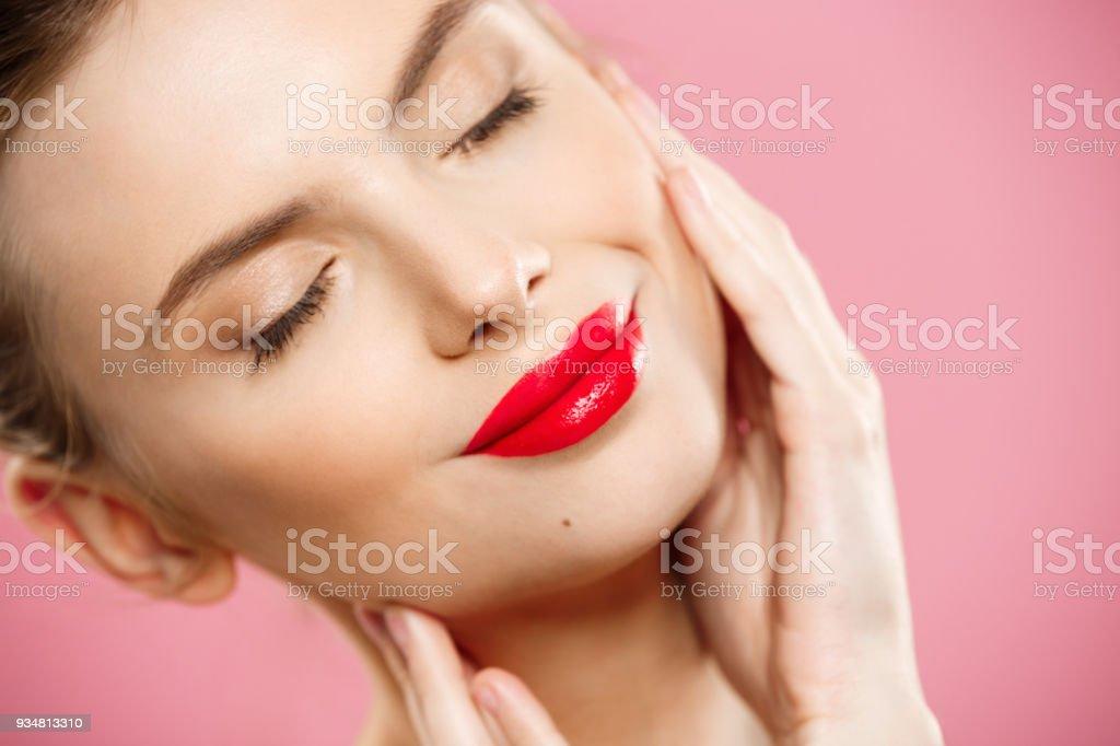 뷰티 개념-화려한 젊은 갈색 머리 여자 얼굴 초상화 닫기. 밝은 눈 썹, 뷰티 모델 소녀 그녀의 얼굴을 만지고 메이크업, 붉은 입술, 완벽 한. 분홍색 배경에 절연 - 로열티 프리 사람 얼굴 스톡 사진