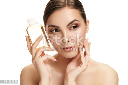 1151624350istockphoto Beauty concept. The pretty woman with perfect skin holding oil bottle 1094432698