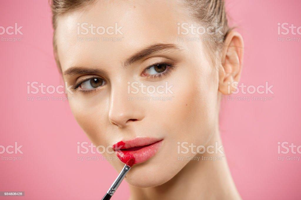 뷰티 개념-핑크 스튜디오 배경으로 빨간 립스틱을 적용 하는 여자. 아름 다운 여자 화장은. - 로열티 프리 반짝이는 스톡 사진