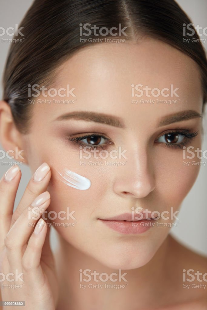 Beauty Cosmetics. Portrait Of Attractive Young Woman Putting Cosmetic...