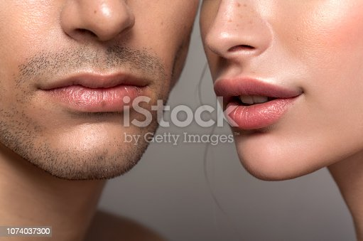 Closeup studio shot of a beautiful young woman and man posing against a grey background