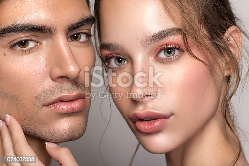 Closeup studio shot of a beautiful young woman and man with freckles skin posing against a grey background