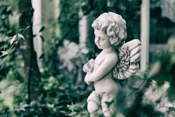 Beauty Cupid statue of Angel in vintage garden on summer. Holding bouquet flowers in his hand - foto de stock