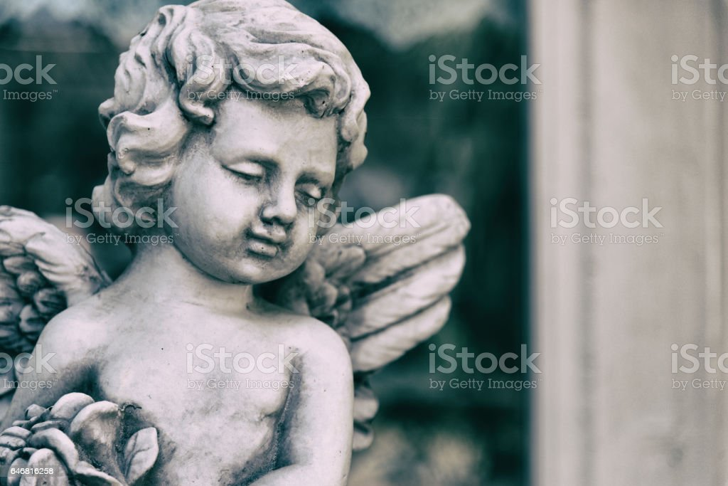 Beauty Cupid statue of Angel in vintage garden on summer. Holding bouquet flowers in his hand stock photo