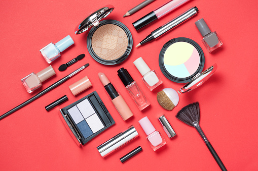 Beauty, decorative cosmetics. Makeup brushes set and color eyeshadow palette on pink and blue background , flat lay, top view, Minimalistic style.red background.