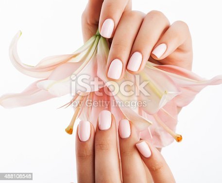 istock beauty delicate hands with manicure holding flower lily close up 488108548