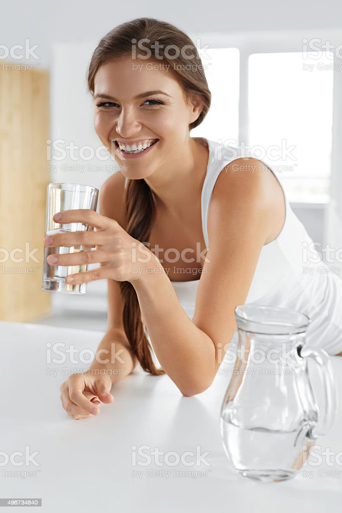 Beauty, Diet Concept. Happy Smiling Woman Drinking Water. Health stock photo