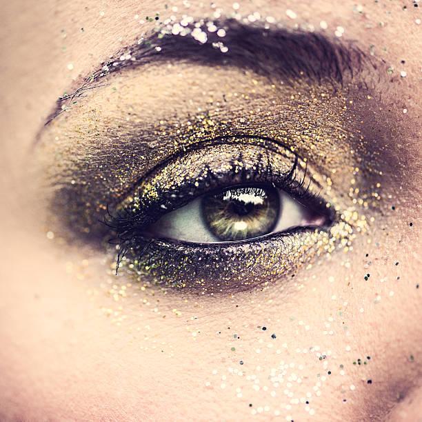 schönheit auge nahaufnahme mit glitzer - goldenes augen make up stock-fotos und bilder