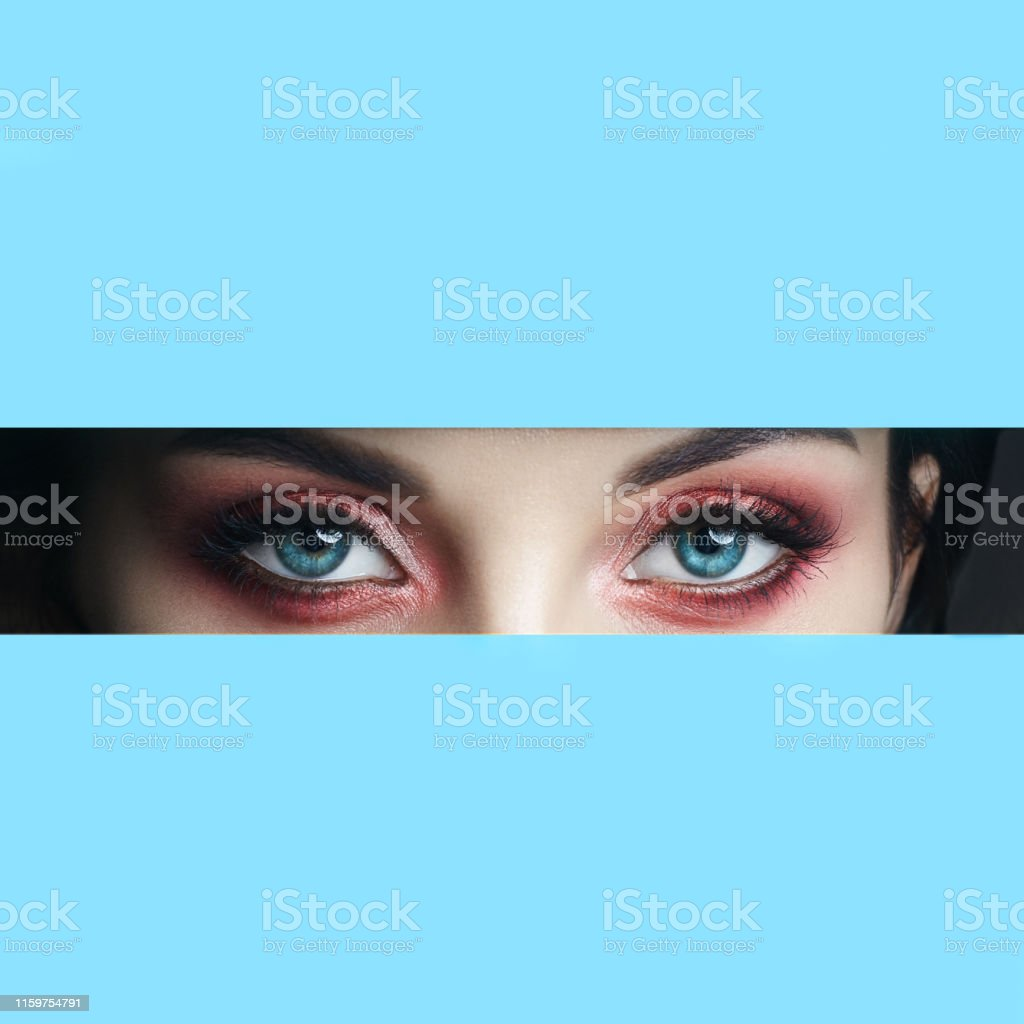 Beauty Face Red Makeup Eyes Of A Young Girl In A Slit Hole Of Blue Paper Woman With Beautiful Makeup Red Glowing Shadow Big Blue Eyes In The Slit Hole Stock Photo