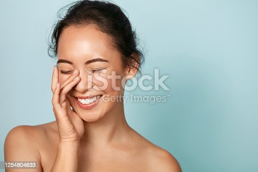 istock Beauty face. Smiling asian woman touching healthy skin portrait 1254804633