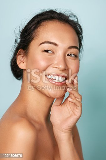 istock Beauty face. Smiling asian woman touching healthy skin portrait 1254806678
