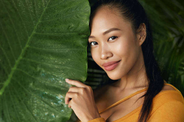 Beauty face. Woman model with natural makeup behind green leaf – zdjęcie