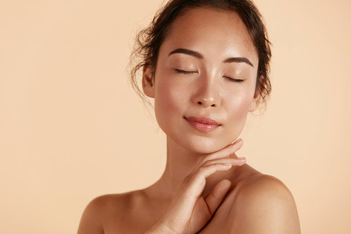 Beauty face. Woman with natural makeup and healthy skin portrait. Beautiful asian girl model touching fresh glowing hydrated facial skin on beige background closeup. Skin care concept
