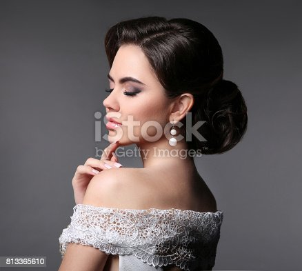 Beauty fashion bride makeup. Elegant fashionable woman portrait. Retro hair style. Brunette model with pearl earrings isolated on dark grey studio background.