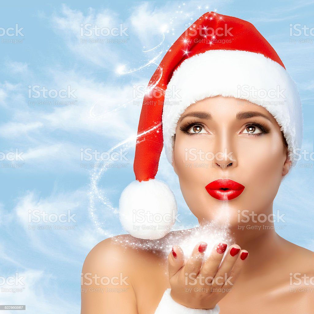 Beauty Fashion. Christmas Woman in Santa Hat Blowing Sparkling Stardust stock photo