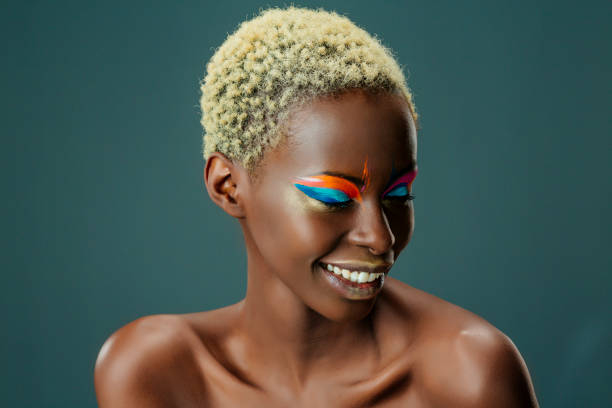 Beauty, fashion portrait. Original looks. Beautiful, lovely and sensual young african girl. Attractive African ethnicity, slim women, blonde, short hair. Gray wall background. stock photo
