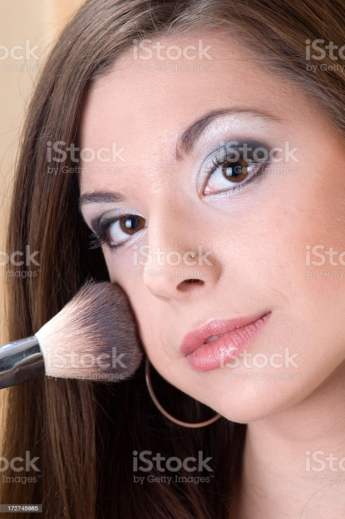 Beauty female applying blusher on her cheeks royalty-free stock photo