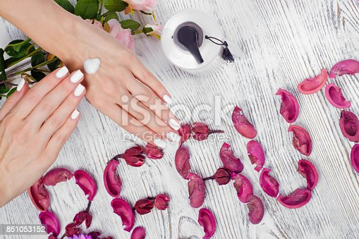 1151624350istockphoto Beauty female hands cream for hands flowers 851053152